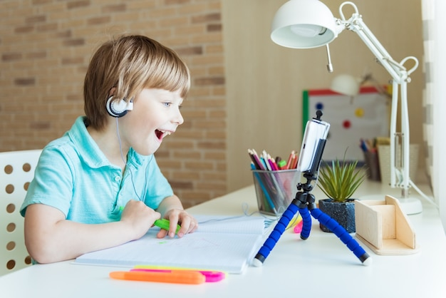 Beautiful creative boy is creativity and the artist in an online drawing paints lesson. childrens creativity. the concept of distance learning online school for the period of global quarantine