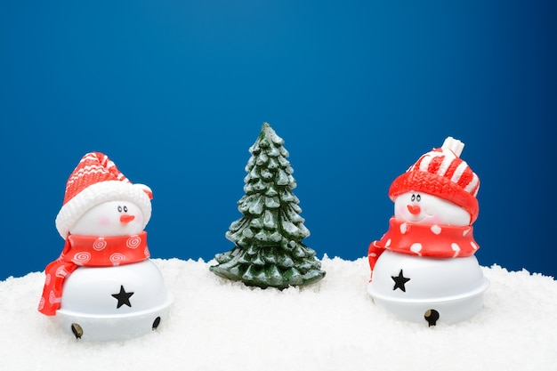 Beautiful creative composition of decorative snowmen with a pine tree on snow with a blue background.
