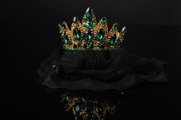 Beautiful crown, feminine head ornament with green stones on a black background with reflection