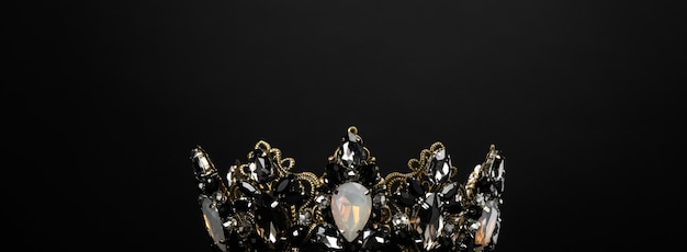 Beautiful crown with black and opal stones on a black background