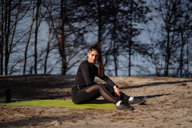 Красивая кавказская брюнетка в спортивной одежде сидит на коврике на природе