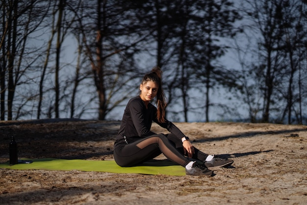 Beautiful cucasian brunette dressed in sports clothing sitting on mat in nature