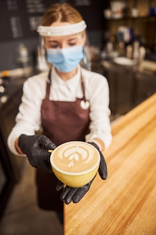 Beautiful cup of coffee in hands of caring barista