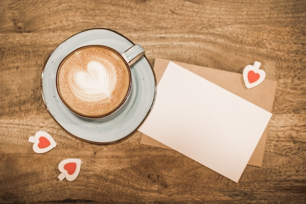 Beautiful cup of coffee with a heart shape, craft envelope, white blank sheet of paper on a wooden background. valentine's day concept. selective focus.