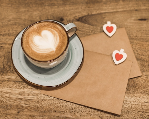 Beautiful cup of coffee with a heart shape and craft envelopes on a wooden background. valentine's day concept. selective focus.