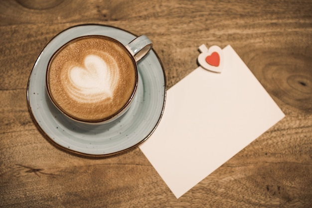 Beautiful cup of coffee with a heart shape and white blank sheet of paper on a wooden background. valentine's day concept. selective focus.