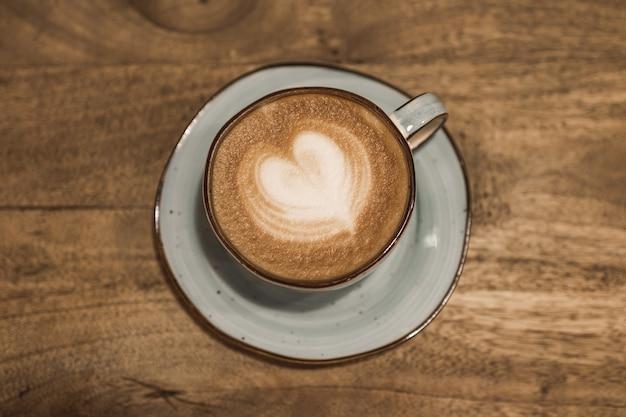 木製の背景にハートの形をした美しい一杯のコーヒー。あなたのテキストのための場所。バレンタインデーのコンセプト。セレクティブフォーカス。