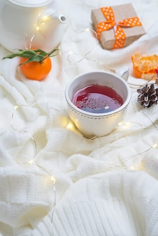 Beautiful cup of tea with tangerines on knitted white warm blanket
