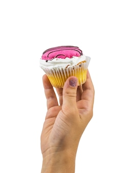 白い背景で隔離の赤ちゃんの手の美しいカップケーキ。お子様の手で作りたての自家製甘さ。