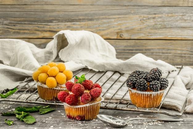 木製の背景に果実と美しいカップケーキ
