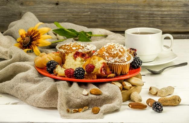 Красивые кексы с ягодами на деревянной стене в красной тарелке