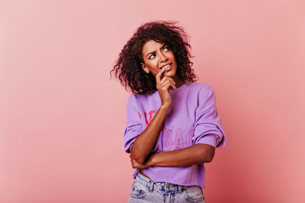 뭔가 대해 생각하는 아름 다운 호기심 아프리카 소녀. 빛에 포즈를 취하는 웅장한 흑인 아가씨.