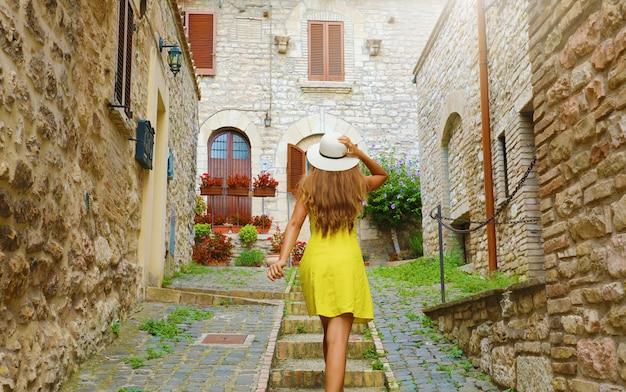 黄色のドレスと帽子を持つ美しい好奇心旺盛な若い女性は、アッシジ、イタリアの通りの2階に行きます。イタリア中部を訪れる幸せな陽気な女の子の後姿。