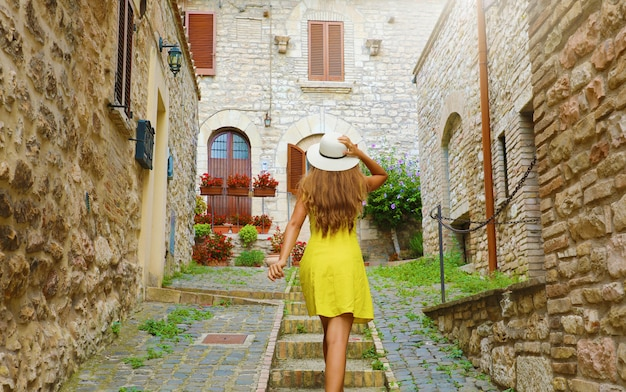 Beautiful curious young woman with yellow dress and hat goes upstairs in street in assisi, italy. rear view of happy cheerful girl visiting central italy.