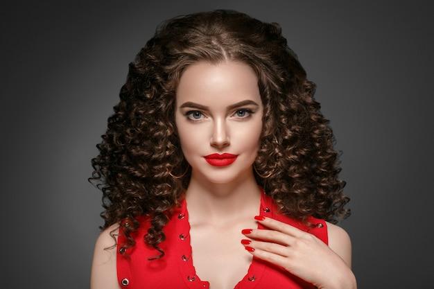 붉은 입술과 드레스 매니큐어, 아름다운 붉은 아프로 헤어스타일을 한 아름다운 곱슬머리 여성. 스튜디오 촬영.