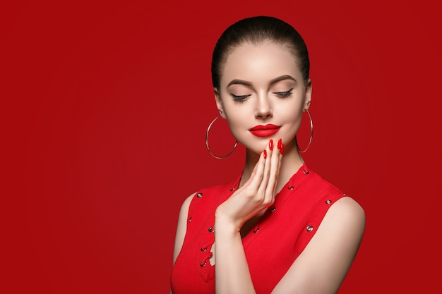 붉은 입술과 드레스 매니큐어가 있는 빨간색의 아름다운 곱슬머리 여성, 붉은 배경 위에 아름다운 장미 아프로 헤어스타일. 스튜디오 촬영.