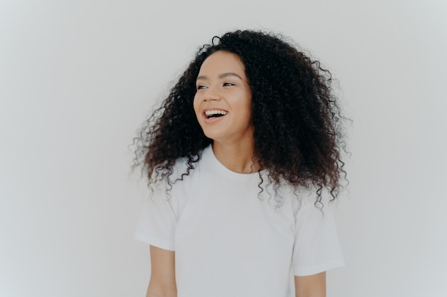 Beautiful curly adult woman turns gaze aside has glad expression smiles and laughs at something funny