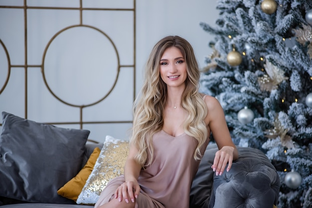 Beautiful curly blonde girl sits on gray sofa, her smile with white teeth over christmas tree