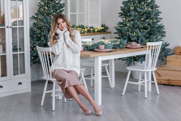 光の花輪とクリスマスツリーのそばに長い髪の美しい巻き毛のブロンド。大きな襟付きのグレーのニットセーターに身を包んだ陽気な女の子の笑顔、粉っぽいドレスがキッチンに座っています