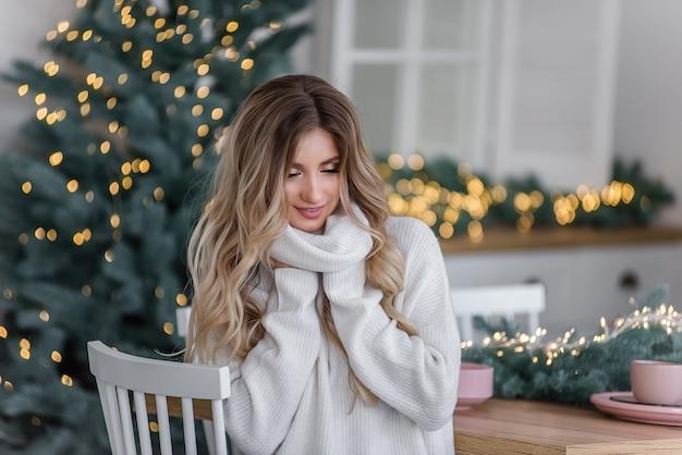 光の花輪とクリスマスツリーのそばに長い髪の美しい巻き毛のブロンド。大きな襟付きの灰色のニットセーターで白い笑顔の女の子のクローズアップの肖像画。コピースペース、テクスチャ