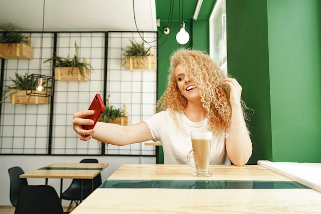 Красивая кудрявая блондинка делает селфи, сидя за столом в кафе