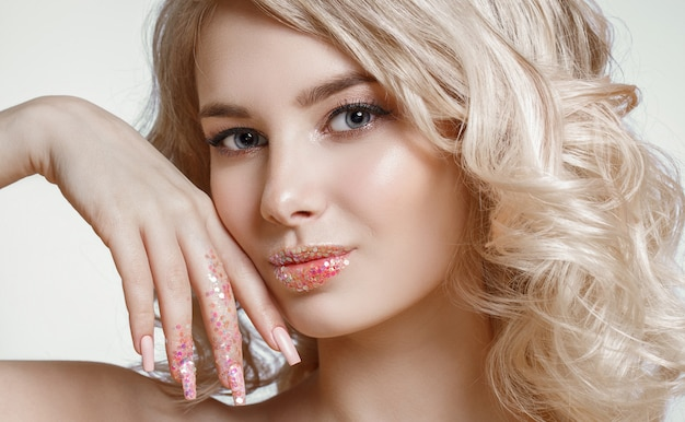 Beautiful curly blonde woman with perfect art make-up, trendy frosted nail design with glitter.