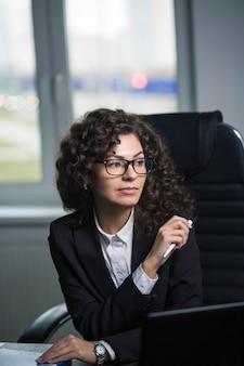 オフィスの職場で眼鏡をかけている美しい巻き毛のブルネットの実業家