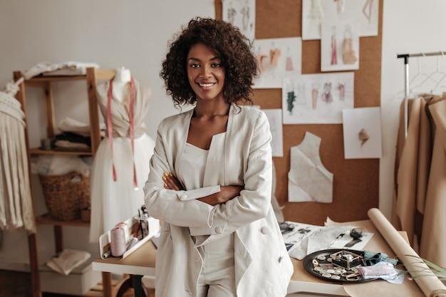 美しい巻き毛のブルネットの浅黒い肌のファッションデザイナーがオフィスでポーズをとって、テーブルに寄りかかる