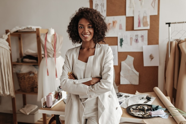 Beautiful curly brunette dark-skinned fashion designer poses in office, leans on table