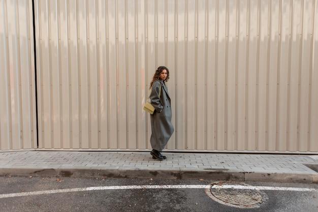 가방을 들고 패션 빈티지 옷을 입은 아름다운 곱슬머리 소녀가 금속 벽 근처를 걷습니다. 여성의 스트리트 스타일과 아름다움