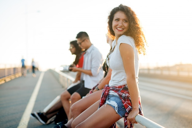 Красивая кудрявая девушка отдыхает на улице со своими друзьями.