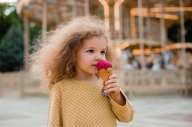 민족 드레스에 아름 다운 곱슬 소녀 놀이 공원에서 아이스크림을 먹는다