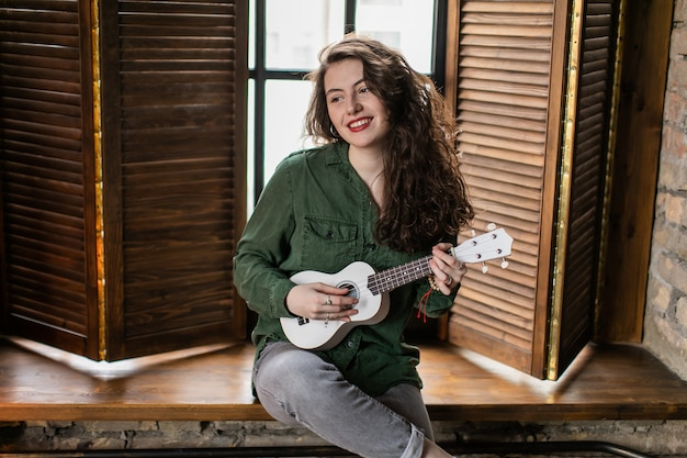 Beautiful curly girl sitting on the window sill in loft apartment, playing white ukulele music instrument and singing songs