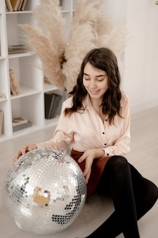 Beautiful curly girl with a mirror ball with a disco ball