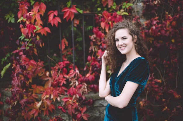 Beautiful curly hair girl in a dark blue velvet dress in an autumn park