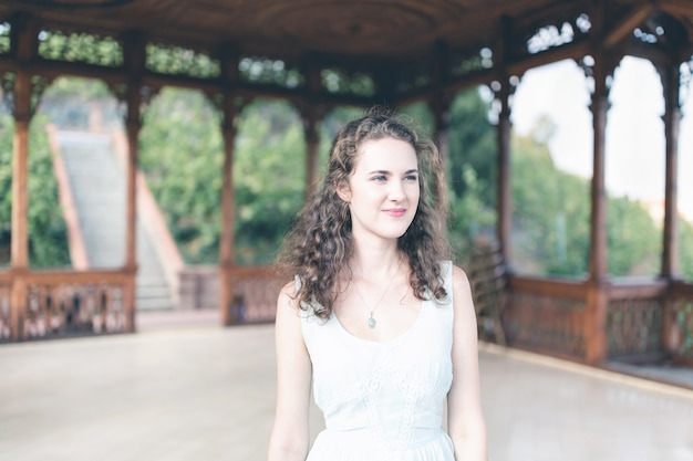 Красивая кудрявая девушка в голубом простом платье в павильоне в саду