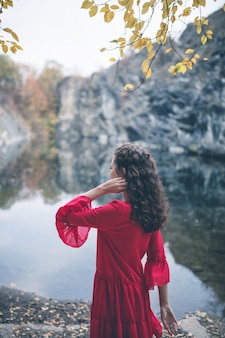 Beautiful curly hair girl in a red dress looking at the lake