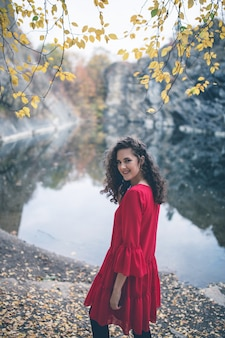 Beautiful curly hair girl in a red dress standing at the lake and smiling