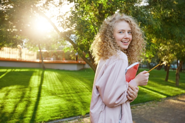 Beautiful curly hair young woman passes by with a red notebook and a pencil in hands