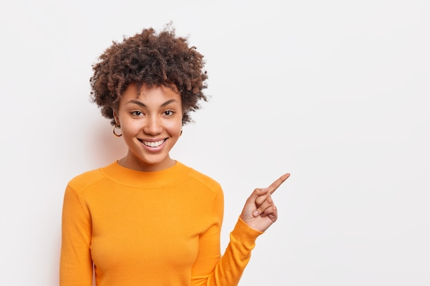 Beautiful curly haired afro american woman suggests to clickon link points on blank copy space shows way stands over white wall wears basic orange jumper. people and advertising concept