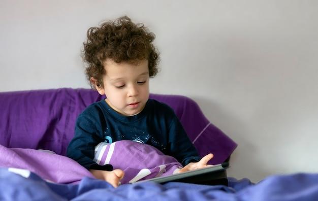 그의 손에 태블릿과 함께 침대에 앉아 아름 다운 곱슬 머리 소년
