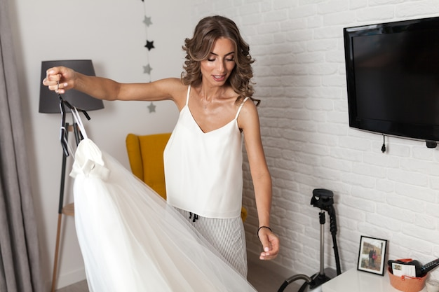 A beautiful curly-haired girl, a future bride measuring a wedding dress in her house before the wedding.