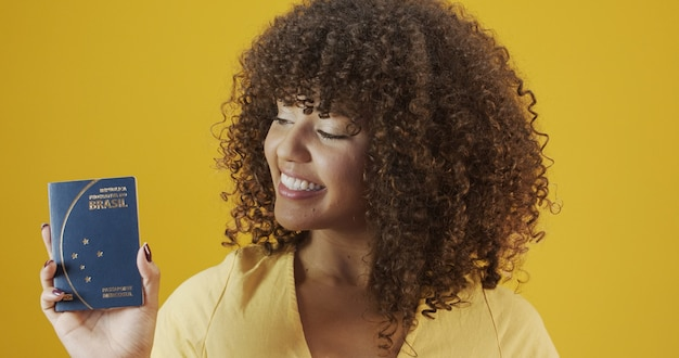 Beautiful curly-haired girl in travel. next trip. girl holding brazilian passport.