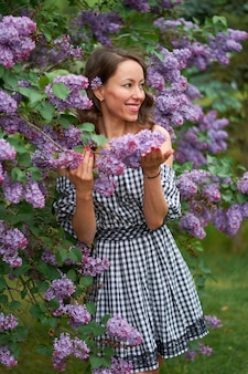 Beautiful curly haired girl with a smile on her face in blooming lilac.