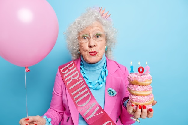 Beautiful curly haired senior woman keeps lips folded enjoys birthday celebration holds pile of delicious doughnuts with candles inflated balloon