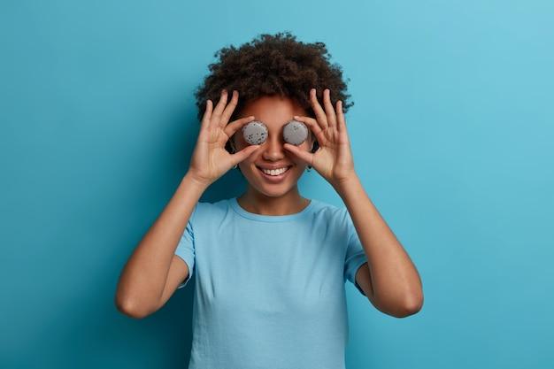 Красивая кудрявая женщина держит на глазах два сладких французских миндального печенья, веселится, радостно улыбается, ест десерты, вкусные кондитерские изделия, носит повседневную синюю футболку, позирует в помещении. сумасшедший сладкоежка