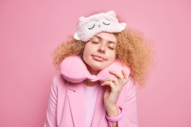 Beautiful curly haired woman sees pleasant dreams while napping during day time keeps eyes closed wears blindfold neck pillow for comfortable rest enjoys calm atmosphere isolated on pink wall