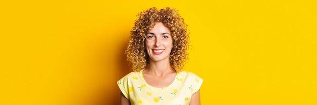 明るい黄色の背景に美しい縮れ毛の若い女性