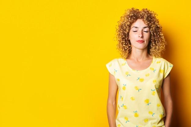 黄色の背景に目を閉じて美しい縮れ毛の若い女性