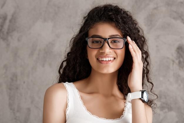 Bella donna ispanica riccia in bicchieri, sorridente